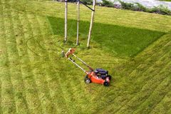 Lawn mower cutting grass on green field in yard. Mowing gardener care work tool.  Royalty Free Stock Photography