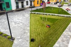 Lawn mower cutting grass on green field in yard near apartment r. Esidential building. Mowing gardener care work tool Royalty Free Stock Photos