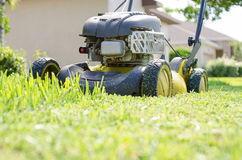 A Lawn Mower Cutting Grass. A lawn mower in the process of cutting the green summer grass Stock Photos