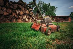 Lawn mower cutting green grass in backyard.Gardening background. Lawn mower cutting green grass in backyard. Gardening background Royalty Free Stock Image