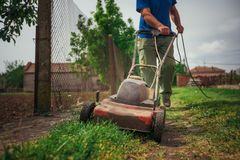 Lawn mower cutting green grass in backyard.Gardening background. Lawn mower cutting green grass in backyard. Gardening background Royalty Free Stock Photo
