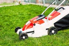 Lawn mower cutting green grass in garden. Royalty Free Stock Photos