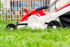 Lawn mower cutting green grass in garden. Spring gardening Stock Images