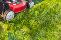 Lawn mower cutting green grass. Work in the garden Royalty Free Stock Photography