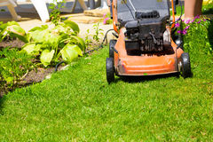 Lawn mower on a fresh lawn in the garden Stock Photos