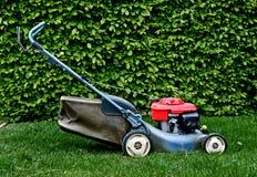 Lawn mower in garden Stock Images