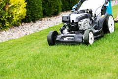 Lawn mower in the garden. Royalty Free Stock Photos