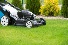 Lawn mower in the garden. Royalty Free Stock Images