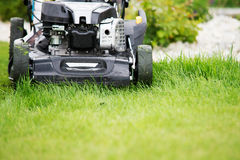 Lawn mower in the garden. Royalty Free Stock Photography