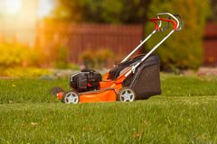 Lawn mower in the garden. Lawn mower in the evening sun shines Royalty Free Stock Photo