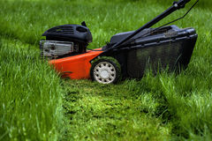 Lawn mower in garden Royalty Free Stock Photos