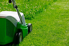 Lawn mower and the grass Royalty Free Stock Images