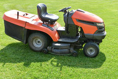 Lawn mower on green field Royalty Free Stock Photo