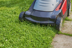 Lawn-mower on green grass Royalty Free Stock Photo