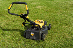 Lawn mower on a lawn. Yellow lawn mower on the green field Royalty Free Stock Image