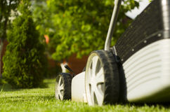 Lawn mower. Lawnmower on the lawn in the rays of the evening sun Royalty Free Stock Images