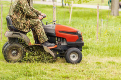 Lawn mower and a man. On a green field Royalty Free Stock Image