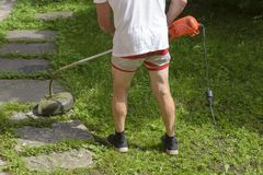 Lawn mower man in shorts in the heat, mow grass trimmer. A stock photos