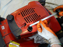 Lawn Mower Oil Check. A man wearing nitrile dipped work gloves is preparing to check the oil in a red lawn mower using a dipstick Stock Image