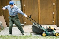 Lawn mower starting 2. Senior starting manually a lawn mower, focus on the tool royalty free stock photography