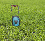 Lawn mower surrounded by high grass. Royalty Free Stock Photo