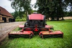 Lawn mower tractor and grass. Red lawn mower tractor machine and green grass Royalty Free Stock Photos