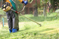 Lawn mower worker cutting grass in green field royalty free stock image