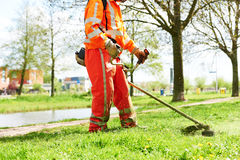 Lawn mower worker man cutting grass Royalty Free Stock Images