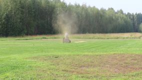 Lawn mower works on big green field. Near forest at summer stock video