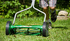 Lawn Mowing. A boy cuts the grass using an non-motorized, non-polluting, push mower stock image