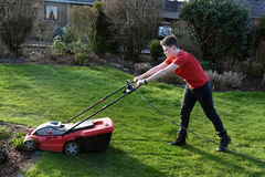 Lawn mowing. Teenage boy cutting grass with the lawn mower Stock Photos
