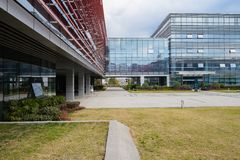 Lawn and open space before building with glassed walls and skybridge in cloudy winter afternoon. The lawn and open space before modern building with glass royalty free stock images