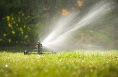 Lawn sprinkler. Spraying water over green grass at summer royalty free stock photos