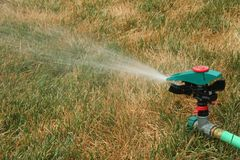Lawn Sprinkler. Watering a dry lawn Stock Images