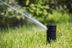 Lawn Sprinkler in Action. Garden Sprinkler Watering Grass. Automatic Sprinklers. Lawn Sprinkler in Action. Garden Sprinkler Watering Grass. Automatic Sprinklers stock photo