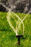 Lawn sprinkler agricultural system working. Blurred water fly in the air. Backlit stock photo