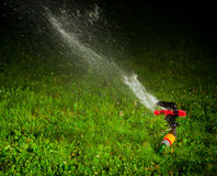 Lawn sprinkler at night Stock Photo