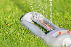 Lawn sprinkler spaying water over green grass. Stock Photos
