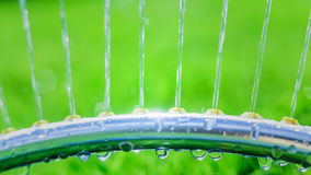 Lawn sprinkler spaying water over green grass Stock Image