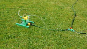 Lawn sprinkler splashing water over green grass stock footage
