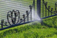 Lawn sprinkler spraying water over green grass and metal fence. Irrigation system - technique of watering in the garden Stock Photo