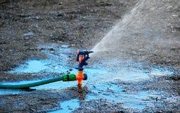 Lawn sprinkler spraying water on soil Stock Images