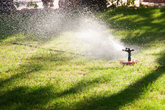 Lawn sprinkler watering the grass Stock Photos
