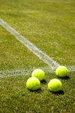 Lawn tennis. 4 tennis balls on a grass court royalty free stock photos