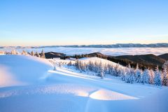 From the lawn with textured snowdrifts there is a view to winter landscape, fair trees in snow,  old huts, high mountains, fog. Royalty Free Stock Photo