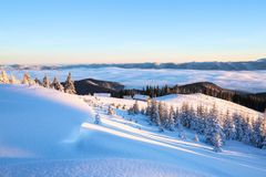 From the lawn with textured snowdrifts there is a view to winter landscape, fair trees in snow,  old huts, high mountains, fog. Stock Image