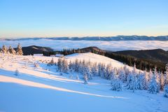 From the lawn with textured snowdrifts there is a view to winter landscape, fair trees in snow,  old huts, high mountains, fog. Stock Photo