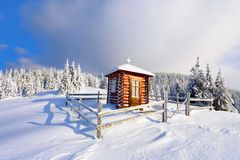 On the lawn there is wooden church covered with snow high on the mountains. Stock Image
