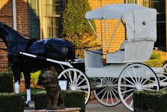 Lawn wagon. Lawn decoration of a black horse pulling a white wagon Royalty Free Stock Images