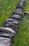 Lawn with wall. Wall of stone in the meadow in bloom Stock Photo